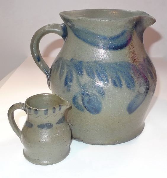 A Present pitcher beside a large decorated pitcher. ai6.
