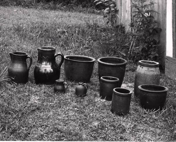 Ten pieces of pottery gathered from the property and displayed on the grass. illus1.