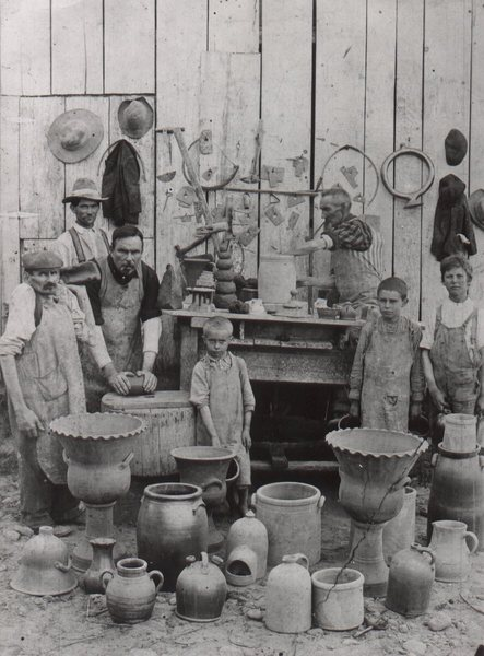 The now famous 1904 Decker Pottery photograph staged outside the pottery showing tools on the wall and finished pieces of pottery. Left to right: William Decker (Uncle Billy), William Duncan, Charles Decker, Jr., a grandson, Charles Sr. at the wheel and two more grandsons. The grandsons, sometimes referred to as apprentices, worked at carrying the pieces to drying racks and other chores. Seen in the Tennessee Conservationist and elsewhere. Burbage2.