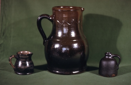 Three pieces of pottery seen in the group of ten on the grass. The small pitcher is basically covered with cobalt and dated on the bottom 1906. Burbage34.